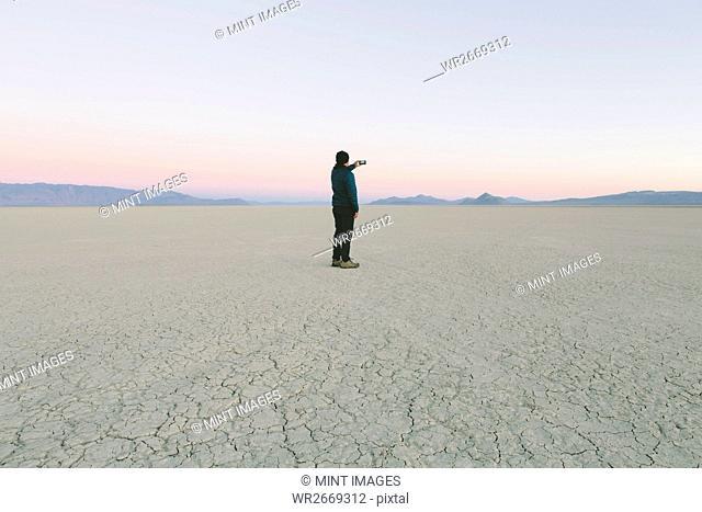 Man taking photo with smart phone, standing in vast desert playa, Black Rock Desert, Nevada