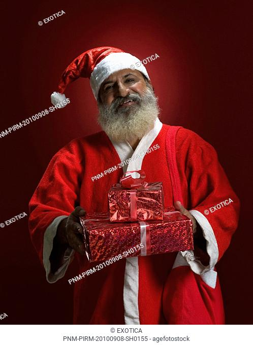 Man dressed as Santa Claus holding presents