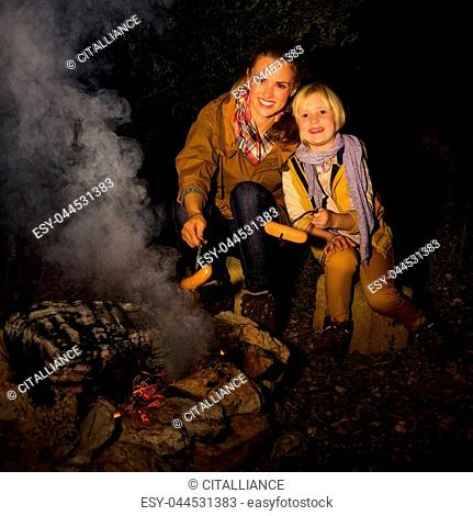 Into the wild. smiling young mother and daughter travellers near a campfire grilling sausages