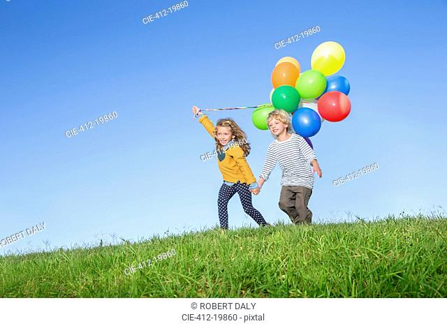 Children with bunch of balloons on grassy hill