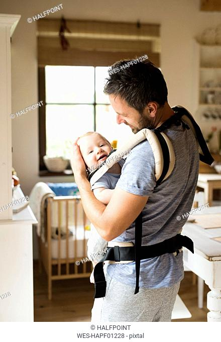 Happy father with baby in baby carrier at home