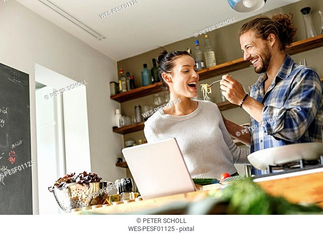 Young couple preparing spaghetti together, using online recipe