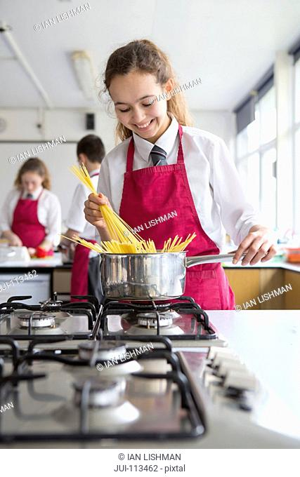 Smiling high school student cooking pasta in home economics class