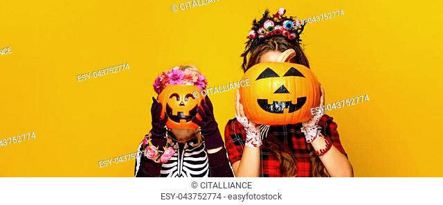 Colorful halloween. modern mother and child in Mexican style halloween costume isolated on yellow background holding jack-o-lantern pumpkins in front of faces
