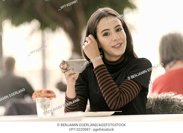 portrait of woman with coffee cup raking hairs while sitting at table in café, in Munich, Germany