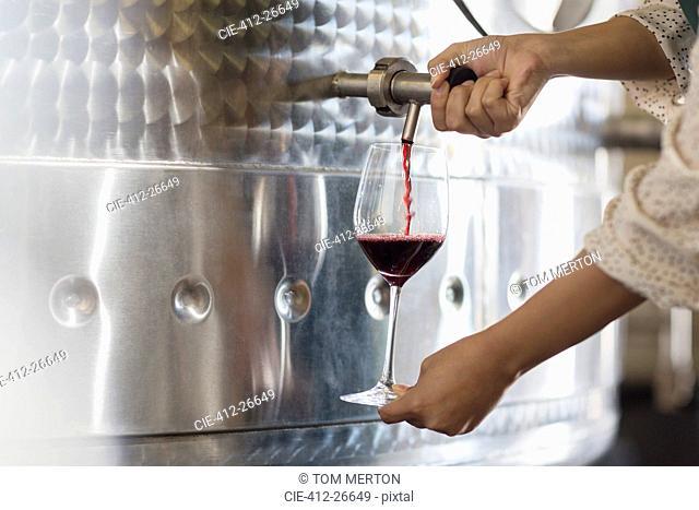 Vintner barrel tasting red wine from stainless steel vat