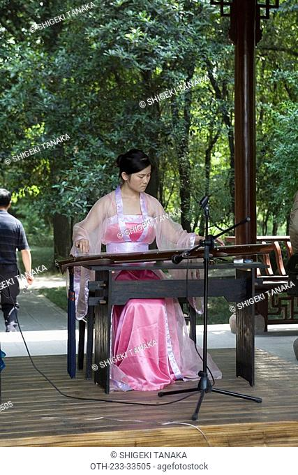 A woman performer playing chinese harp at the thatched cottage of Du Fu at Bamboo Lane, Chengdu, China