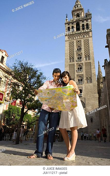 Young couple looking at tourist map by tower, low angle view