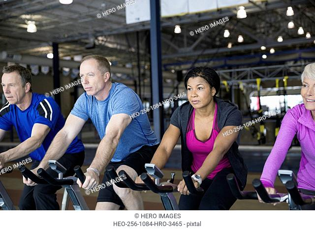 Men and women using exercise bikes at gym
