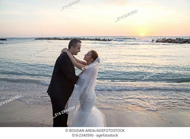 Bride and groom about to kiss on the beach on sunrise/ sunset background