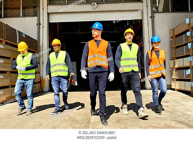 Group of workers walking on factory yard
