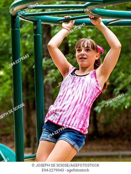 A 12 year old girl hanging with her arms from a jungle gym on a play ground