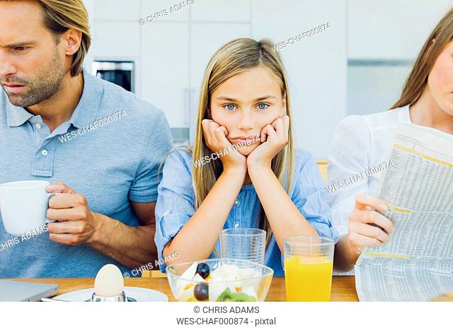 Frustrated girl with distracted parents at breakfast table