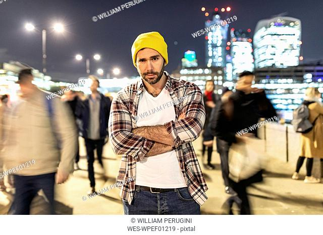 UK, London, portrait of a commuter by night with blurred people passing nearby