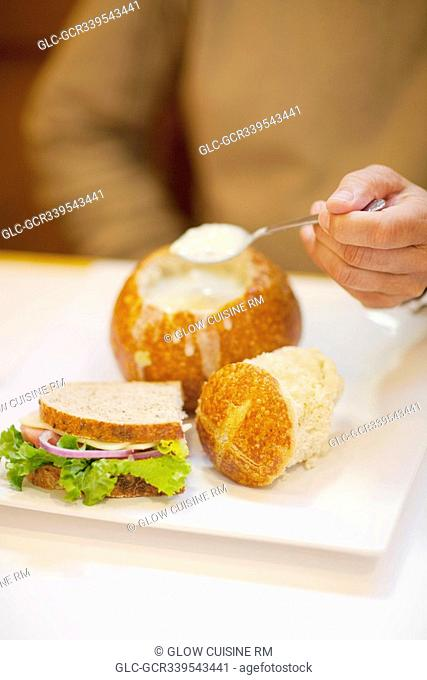 Mid section view of a man eating soup from a bread bowl