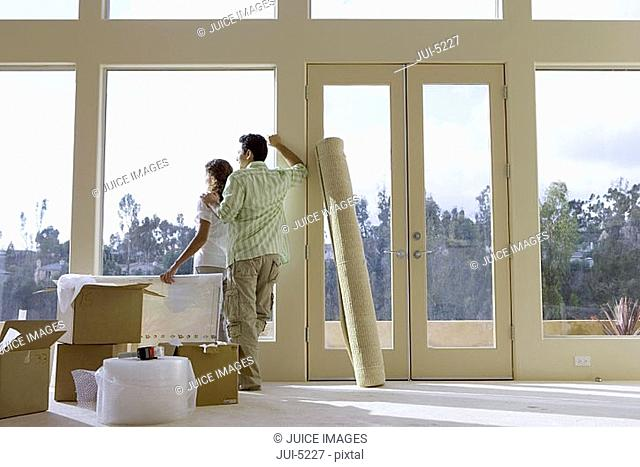 Couple moving house, standing in bare living room with rolled-up carpet and boxes, looking out of window