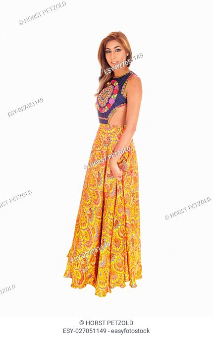 A beautiful young slim woman in a long yellow skirt standing in full .length, isolated for white background.