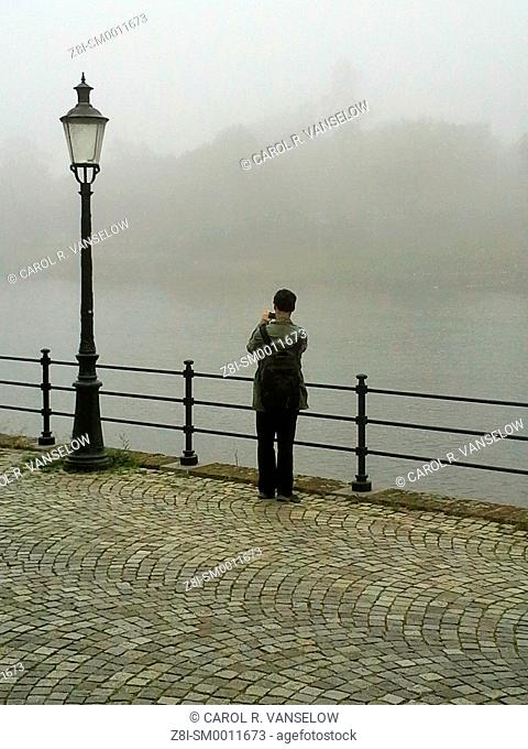 Foggy day by the Maas River in Maastricht. Man taking picture