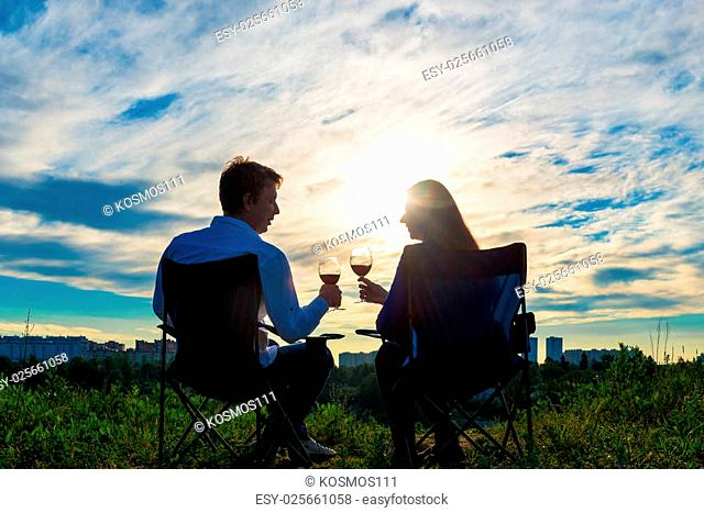 young married couple with a glass of wine at sunset