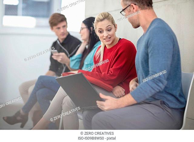 Male and female office workers looking at laptop in meeting