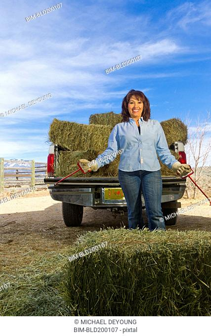 Hispanic woman loading hay onto truck