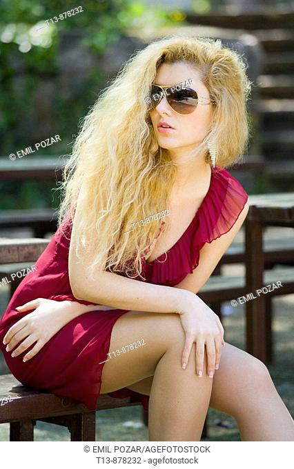 Attractive young woman is sitting on wooden bench in park