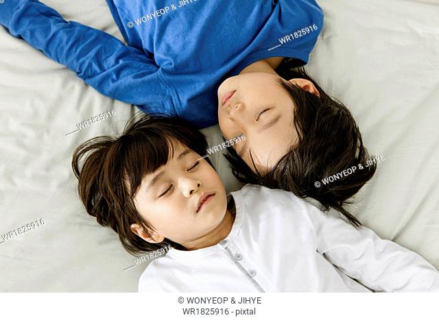 two boys lying on a bed