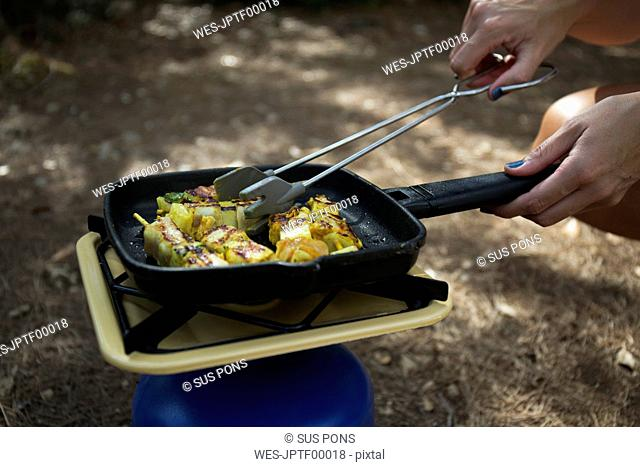 Woman frying vegetable skewer on gas cooker, close-up