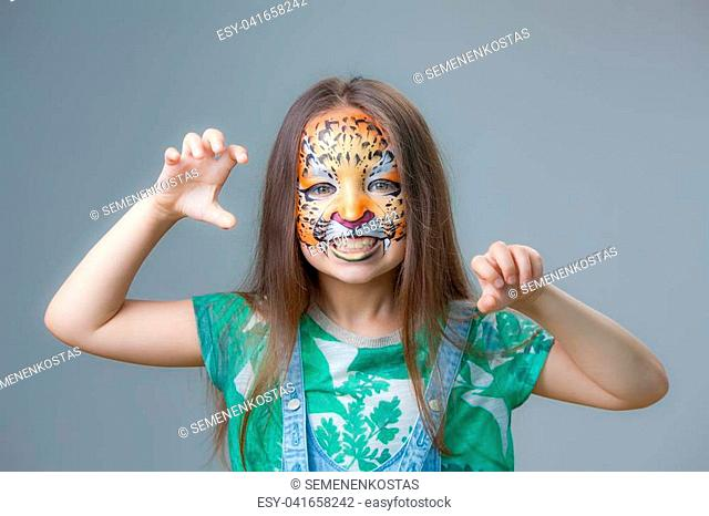Portrait of a little girl with a painted tiger on her face on a gray background