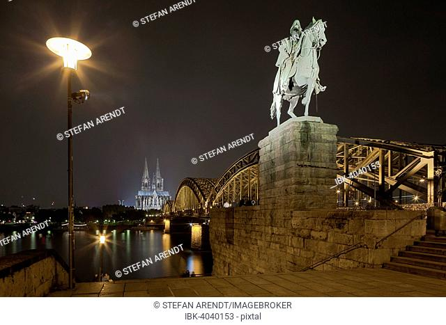 Equestrian statue of Wilhelm I, in back the illuminated Cologne Cathedral and Hohenzollern Bridge at night with Rhine, Deutz, Cologne, North Rhine-Westphalia