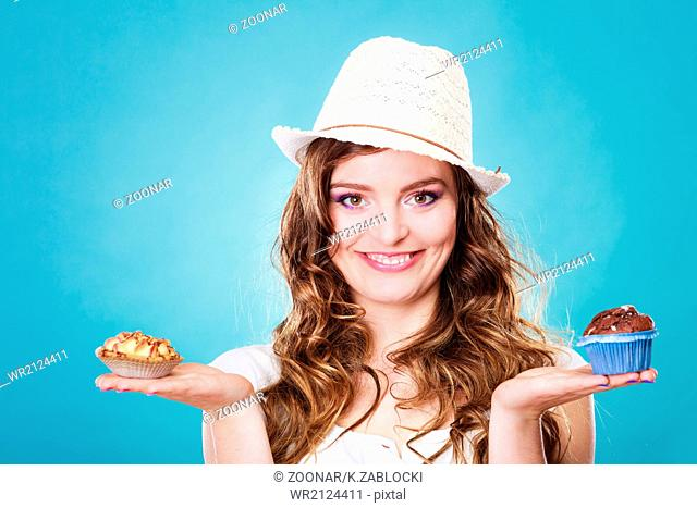 Smiling summer woman holds cakes in hand