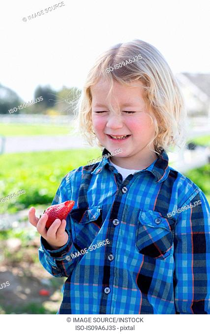 Boy eating strawberry outdoors