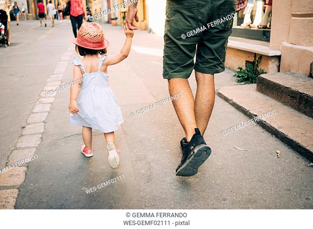 France, Aix-en-Provence, toddler girl and father walking hand in hand in the city