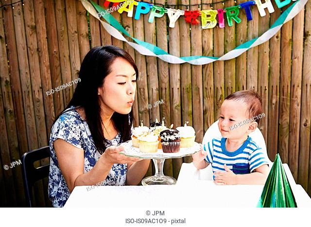 Mother blowing out candles on baby boy's birthday cakes