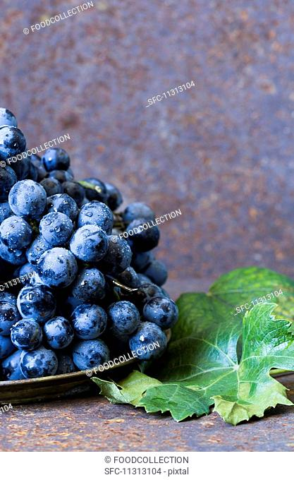 Freshly washed red grapes on a plate next to vine leaves