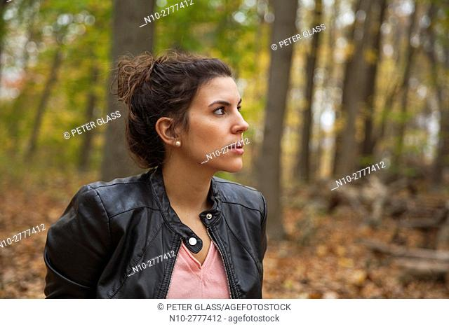 Young woman, wearing a leather jacket, sitting in the woods during autumn