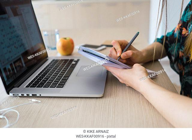 Close-up of woman at home using laptop and taking notes