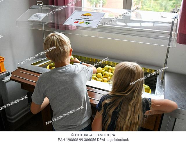 07 August 2019, Berlin: Students take fruit provided for lunch in the canteen of the primary school at Wuhlheide. Photo: Jens Kalaene/dpa-Zentralbild/ZB