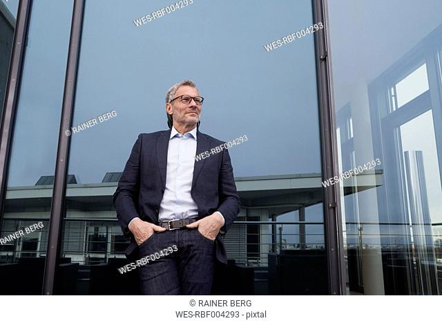 Successful businessman standing on office terrace looking pleased