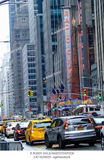 New York. Heavy traffic at Avenue of Americas by Radio City Music Hall that is an entertainment venue at the 1260 of the Avenue, within Rockefeller Center