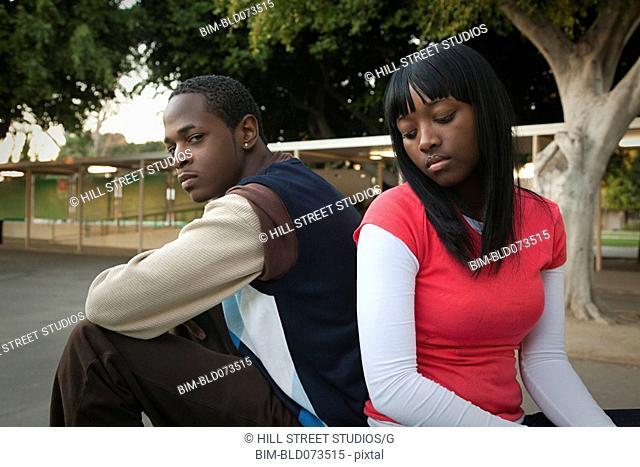 African teenage couple arguing in school yard