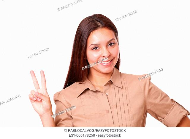 Portrait of cheerful hispanic lady on brown blouse with victory sign smiling at you on isolated studio