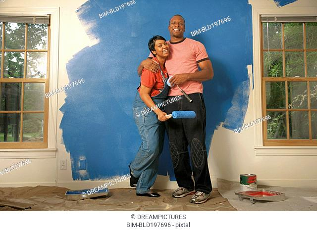 African American couple painting wall