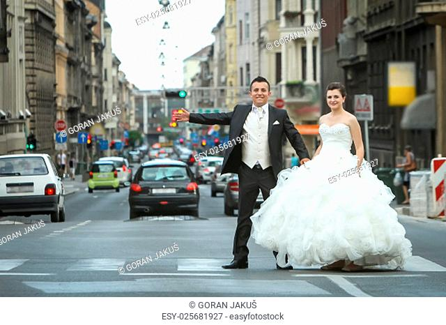 Newlyweds standing on a pedestrian crossing in the middle of the street in city centre and looking at the camera in Zagreb, Croatia