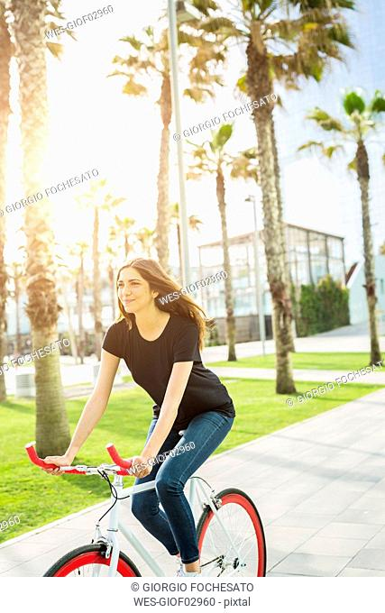 Smiling young woman on fixie bike