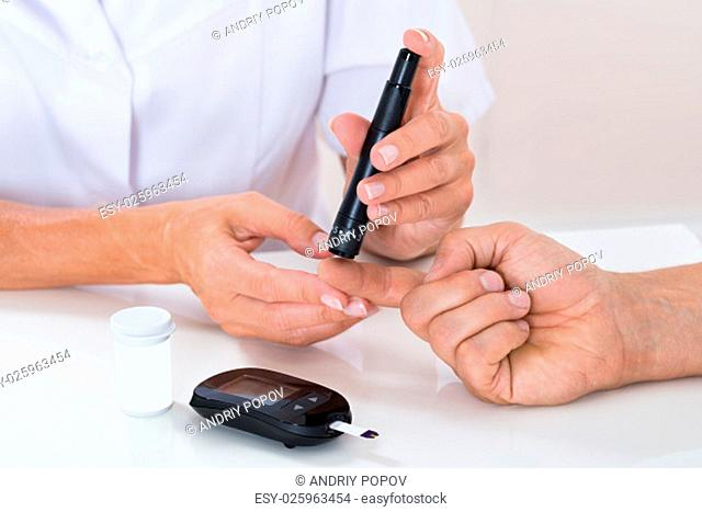 Close-up Of Doctor Measuring Sugar Reading Of Patient With Glucometer