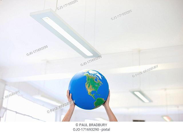 Businessman lifting globe overhead in office