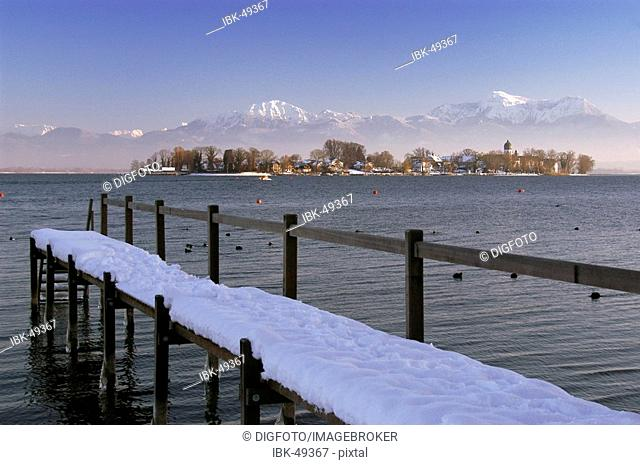 Snowy landing stage in front of Fraueninsel, lake Chiemsee, Bavaria, Germany