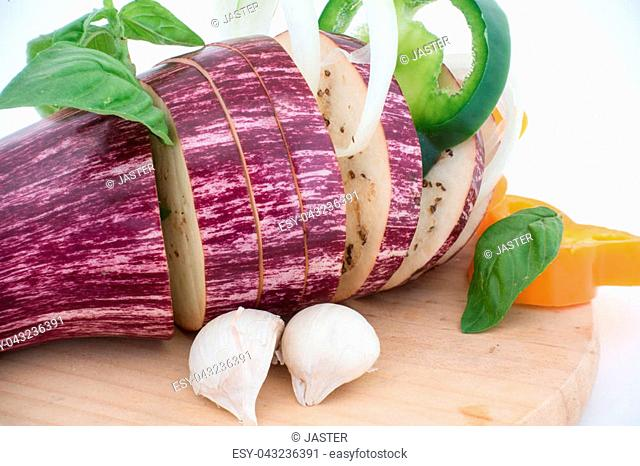 Closeup vegetables composition with garlic, eggplant, basil and orange bell pepper on white background