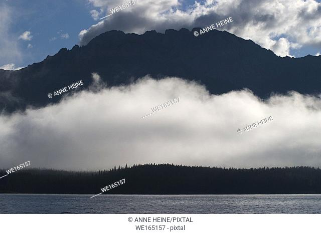 Fog over lakeshore following the outline of the mountain. Kananaskis Lake, Alberta, Canada